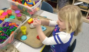Young girl playing with playdoh.